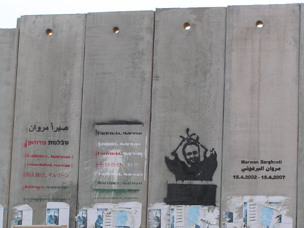 a photo of a graffiti portrait of Marwan Barghouti, bound hands above head, with text on the Israeli West Bank separation barrier, near Qalandia